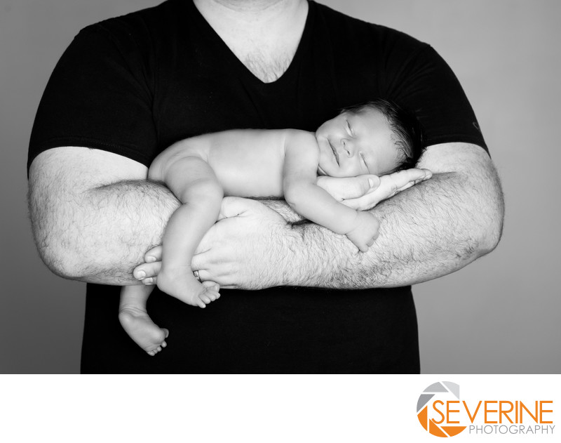newborn pose with father boy black and white