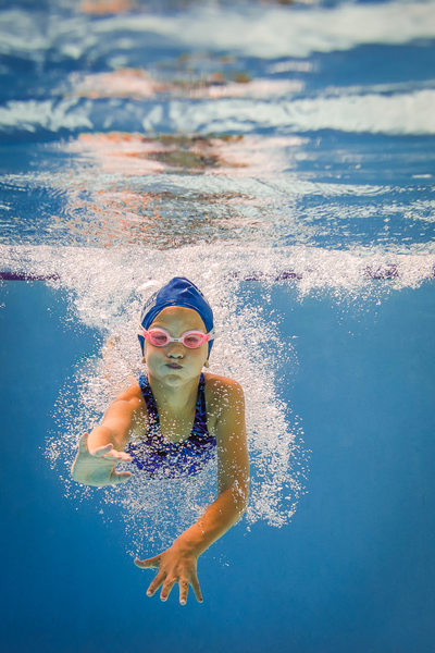 Young swimmer learning her strokes and diving