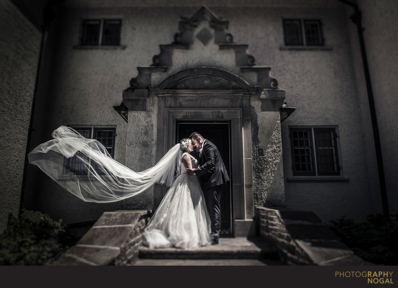 Groom and Bride Hug at Entrance to Adamson Estate