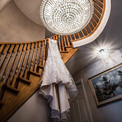 Wedding Dress Hanging Over Railing with Chandelier