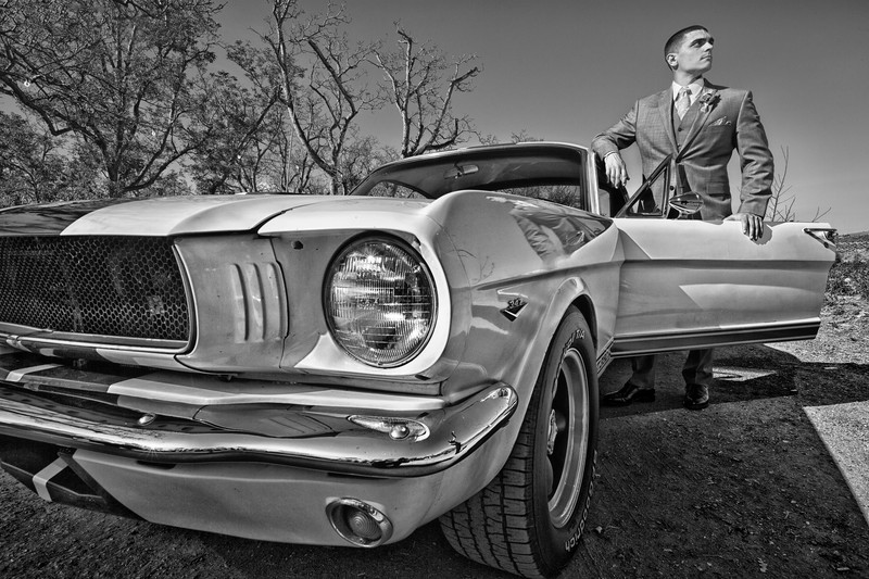 Groom standing by 1965 gt 350 mustang