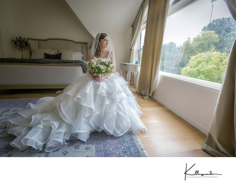 Bride sitting in chair looking out the bridal suit window