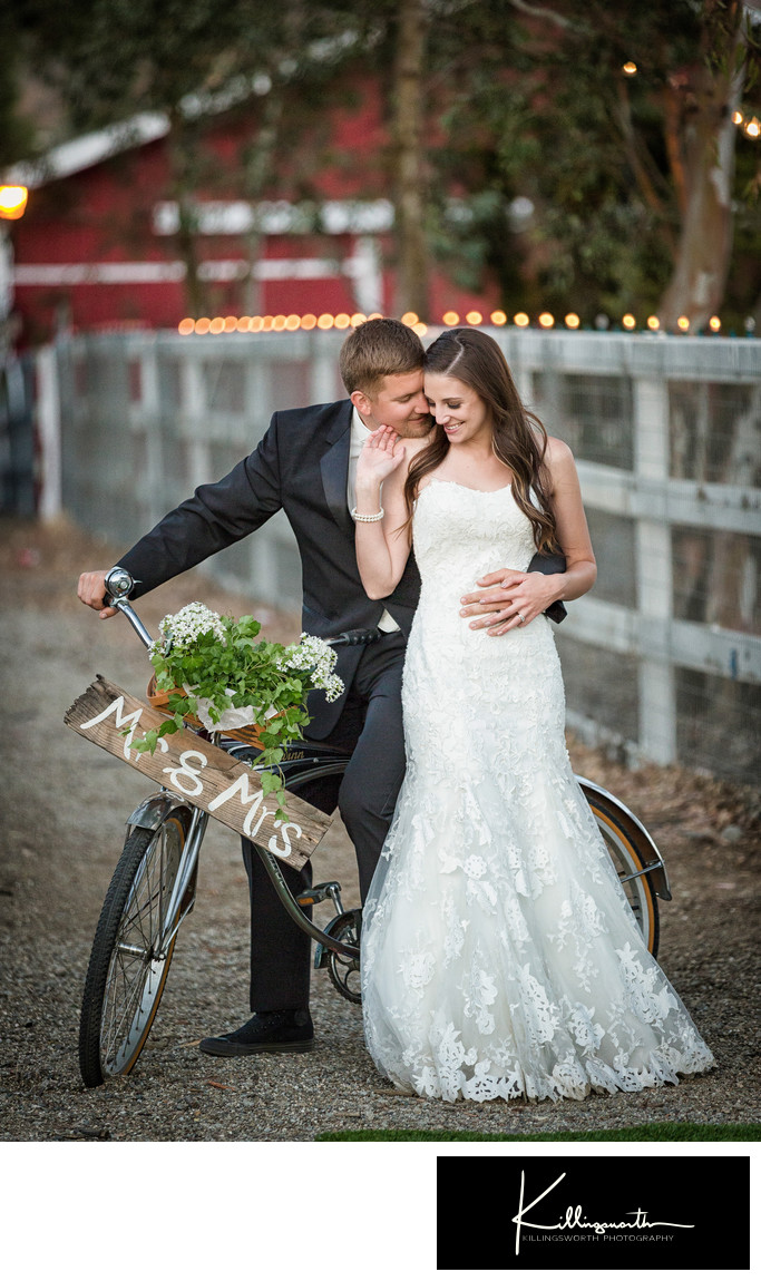 bride and groom posing with bicycle