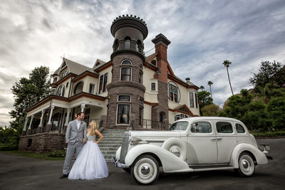 bride and groom in front of newhall mansion with vintage car
