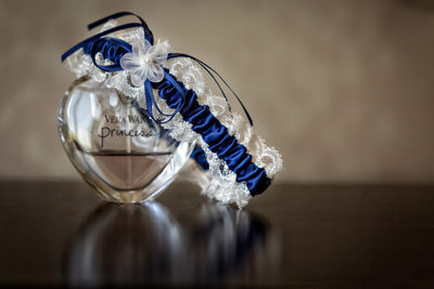 garter laying on top of vera wang perfume bottle