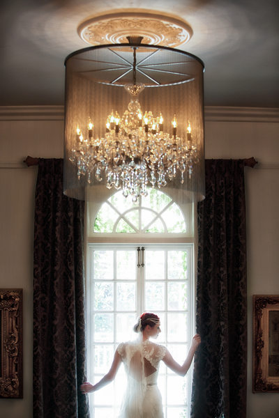bride posing under chandelier and looking out window
