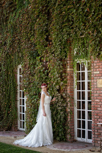 bride posing in front of ivy and brick wall