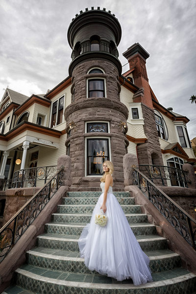 bride standing on front of stairs to newhall mansion