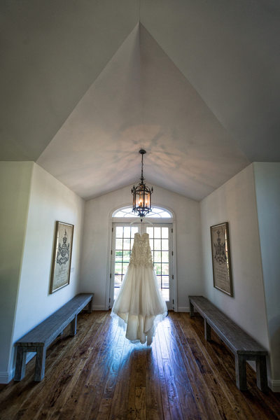 wedding dress hanging in front of villa aix vineyard wedding venue
