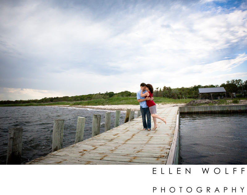 engagement photo on a dock near the beach