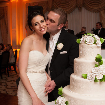 bride and groom next to the wedding cake