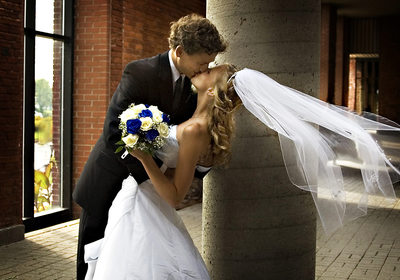 Bride's veil blows in wind as groom sweeps her back in a passionate kiss at their montreal wedding