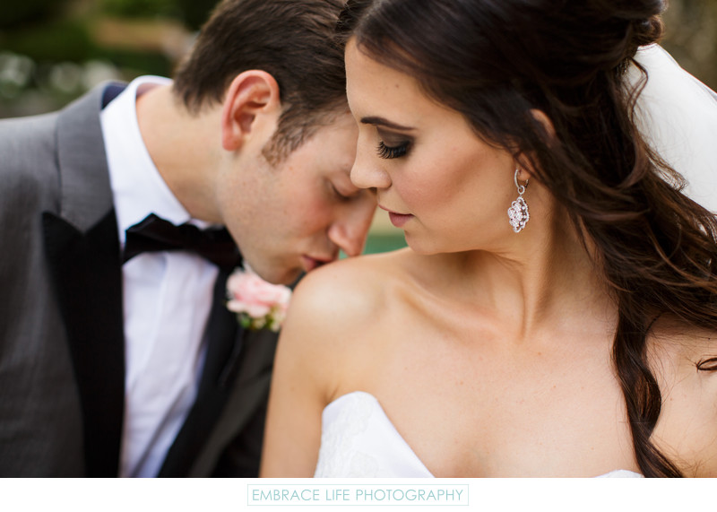 Wedding Photograph of Groom Kissing Bride's Shoulder