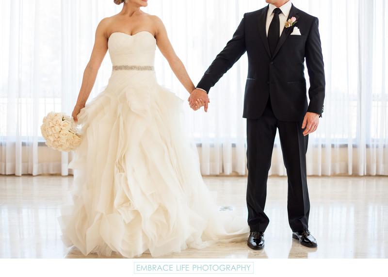 Elegantly Dressed Bride and Groom Holding Hands