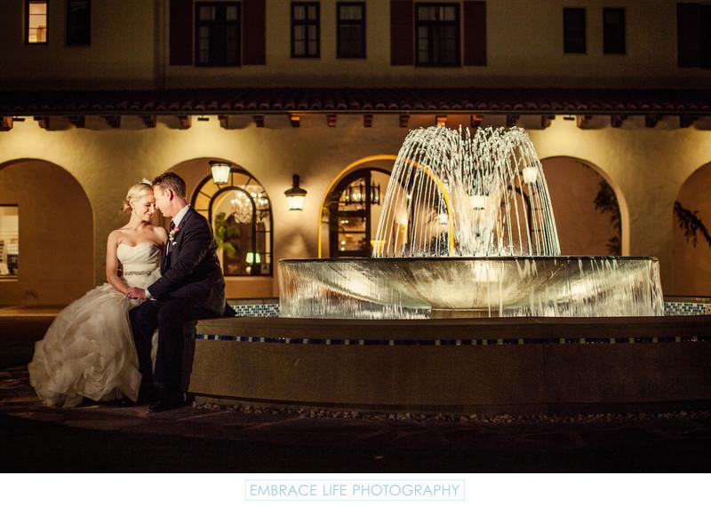 Wedding Couple Sit By Beautiful Garden Fountain