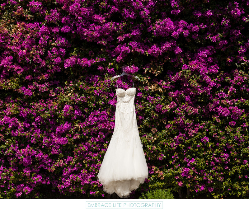 Wedding Dress Hanging on Purple Flower Wall