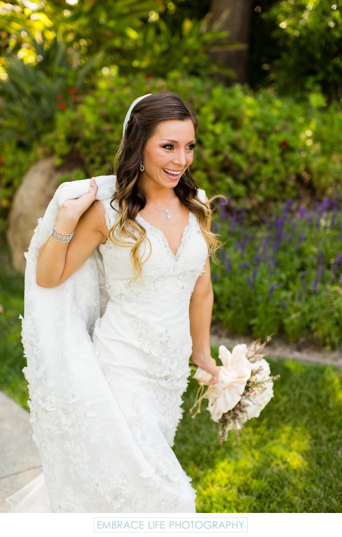 Smiling Bride Holding Up Dress Train
