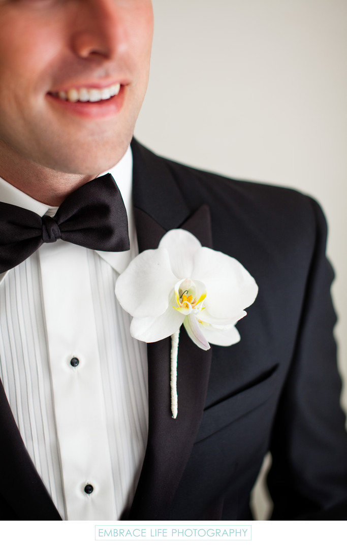White Orchid Boutonniere on Groom's Black Tie Tuxedo