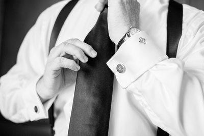 Groom Adjusting Tie With Monogrammed Cufflinks