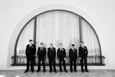 Groom and Groomsmen Pose in Front of Lg Arched Window