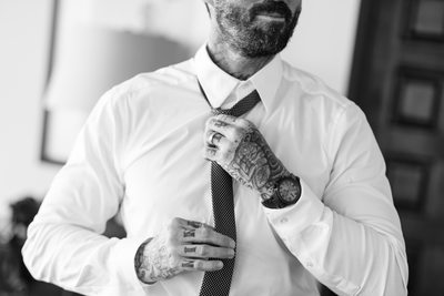 Groomsman with Tattooed Hands Tying Necktie