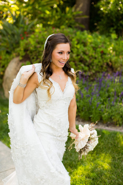 Smiling Bride Holding Up Dress Train