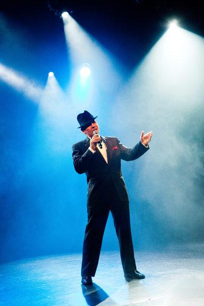 Frank Sinatra Impersonator Singing Under Stage Lighting
