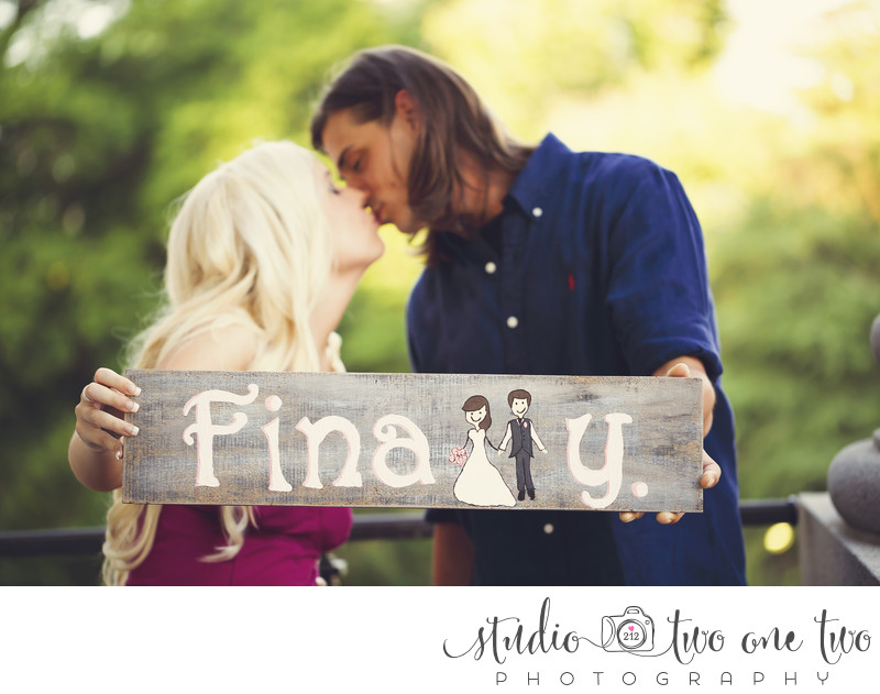 Engagement photo with wooden sign
