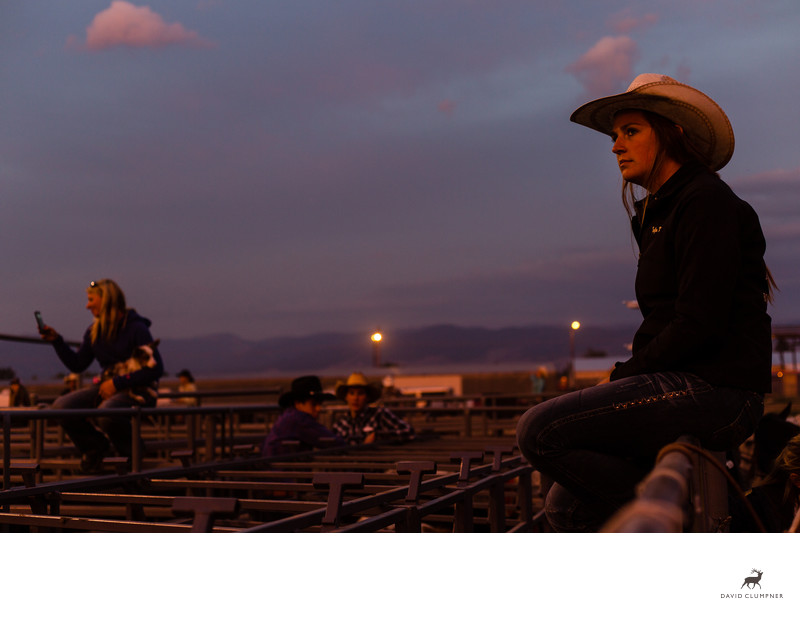 Cowgirl watches Hamilton Rodeo at Sunset