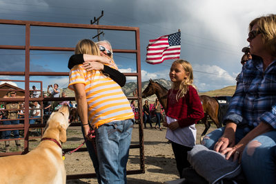 Friends Hug at Beginning of Gardiner Rodeo in Montana