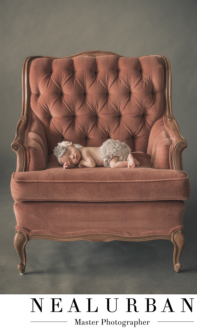 buffalo baby newborn pose in vintage furniture chair