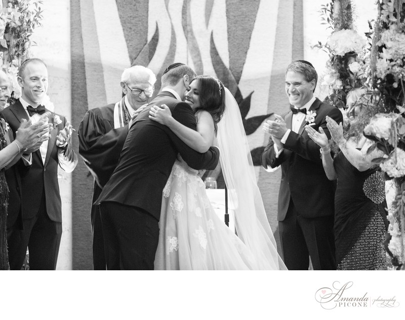 Bride and groom hug at Temple Sinai wedding ceremony