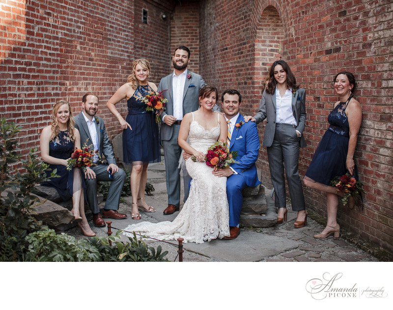 Wedding party posing with brick wall in Brooklyn Heights