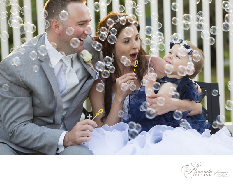 Bride and groom blow bubbles with daughter at wedding