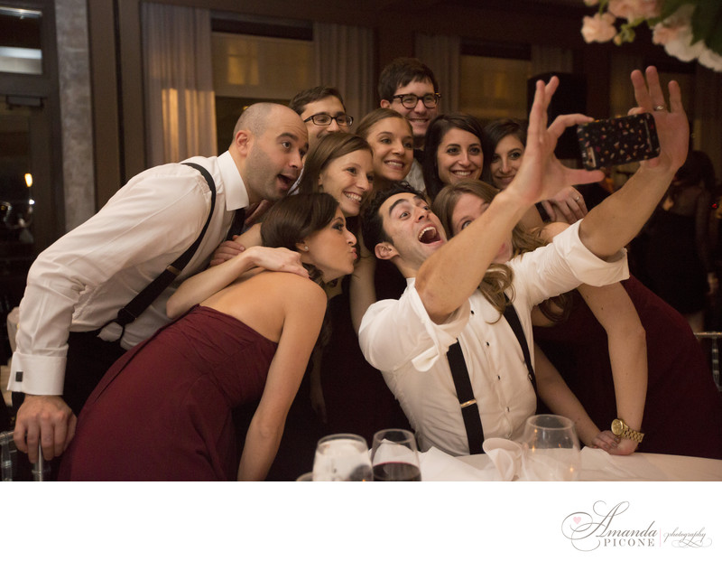 Guests take group selfie at wedding reception