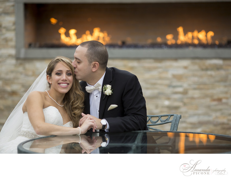 Groom kisses bride by fireplace at Flowerfield Long Island