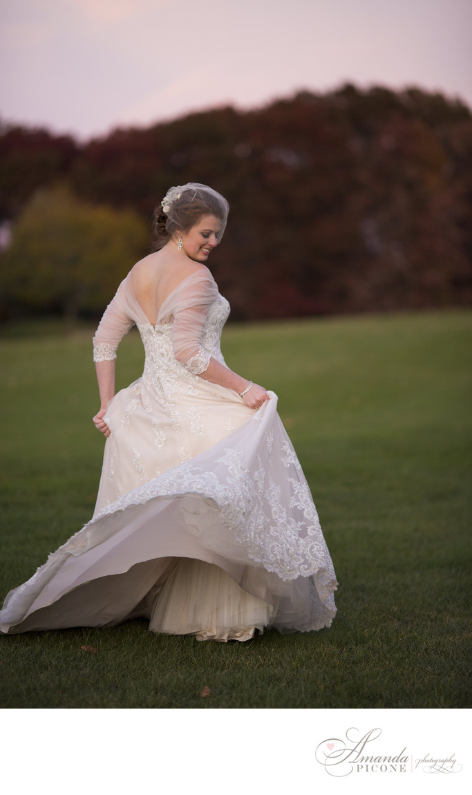 Bride spins in wedding gown on golf course at sunset