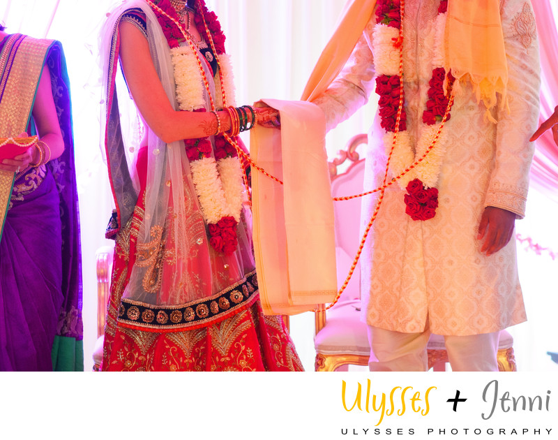 INDIAN BRIDE AND GROOM HOLDING HANDS AT CEREMONY - ULYSSES PHOTOGRAPHY