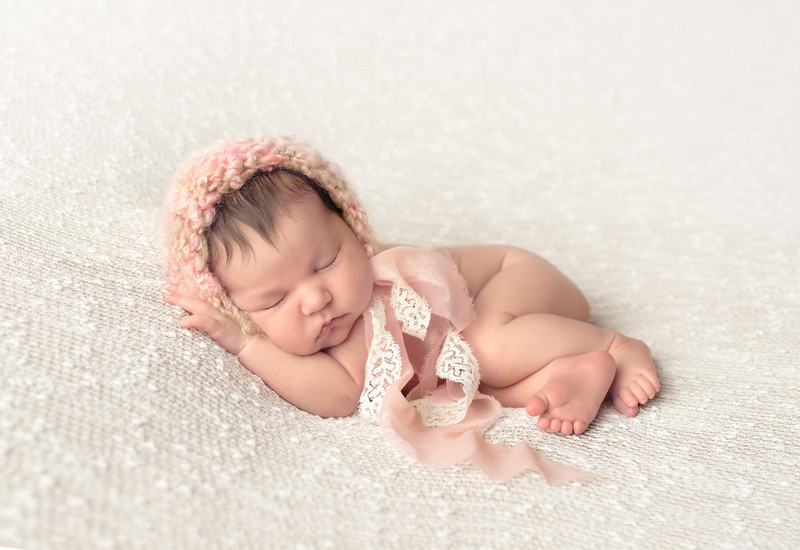 Baby photography with pink and lace ribbons.
