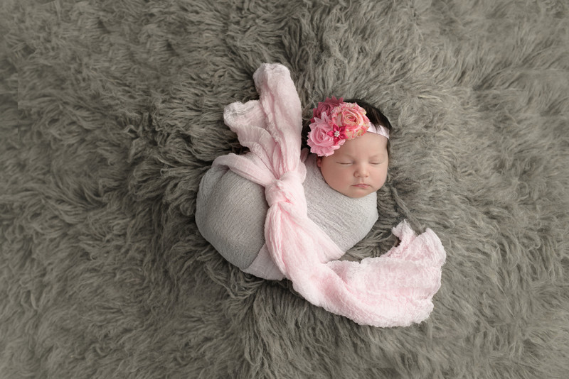 Newborn in pink and gray wrap on Flokati