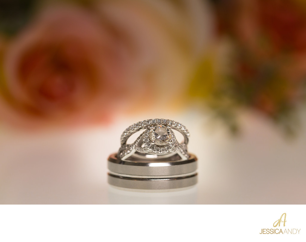 Wedding rings in front of roses by Jessica and Andy