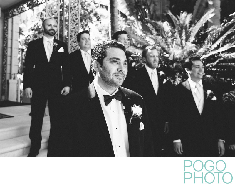 Groom and groomsmen see bride at head of aisle