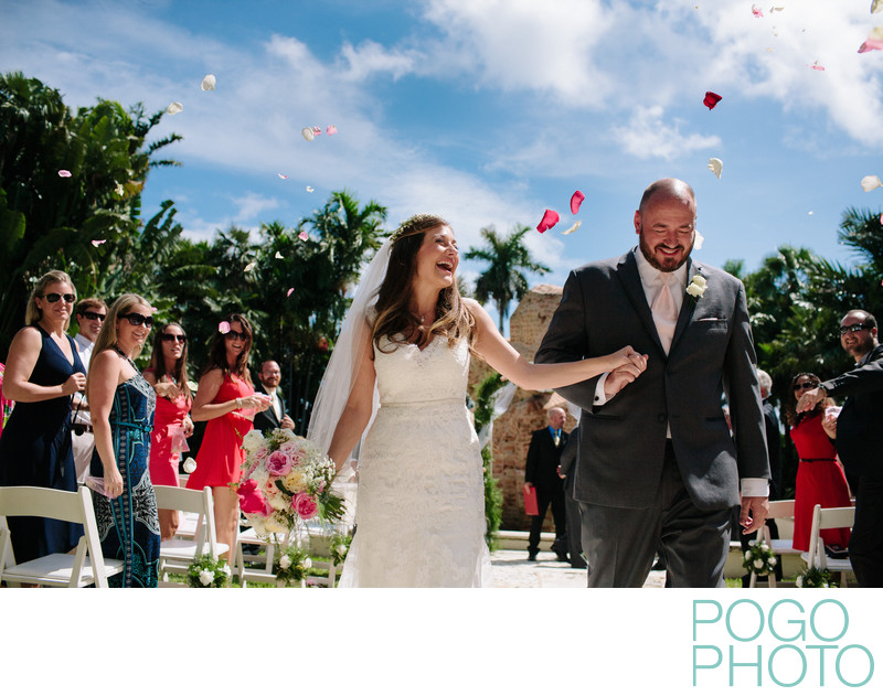 Excited guests toss flower petals on bride and groom