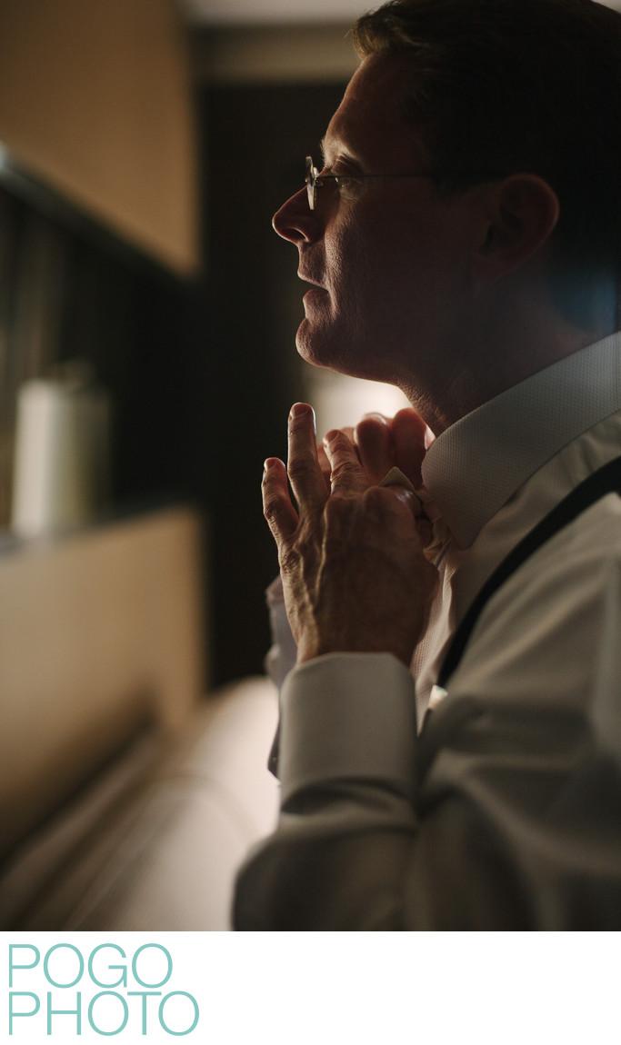 Groom Knots Bow Tie During Destination Wedding in FL