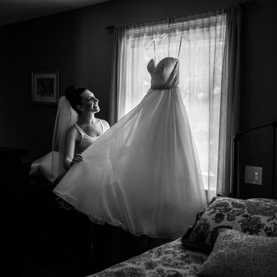 Bride Getting Wedding Dress Down from Window
