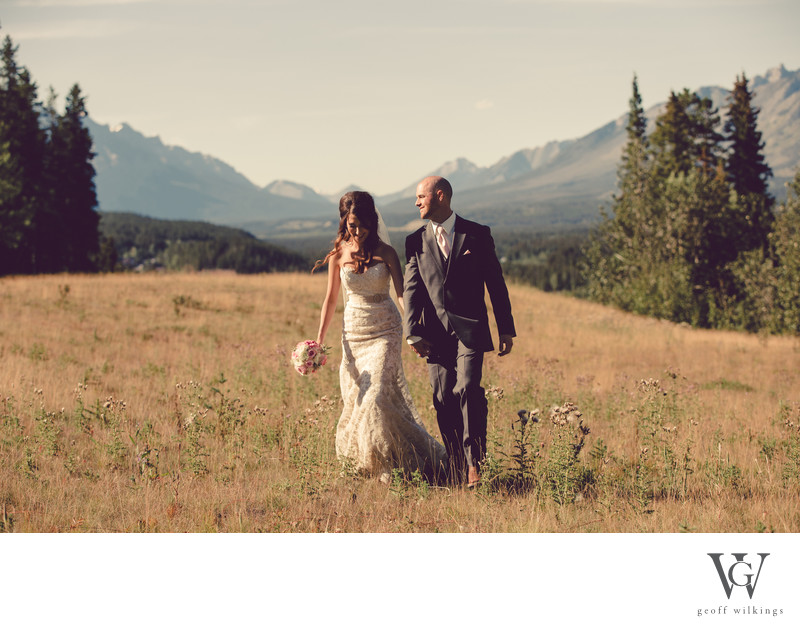Bride + Groom Walking In Canmore Mountainous Area