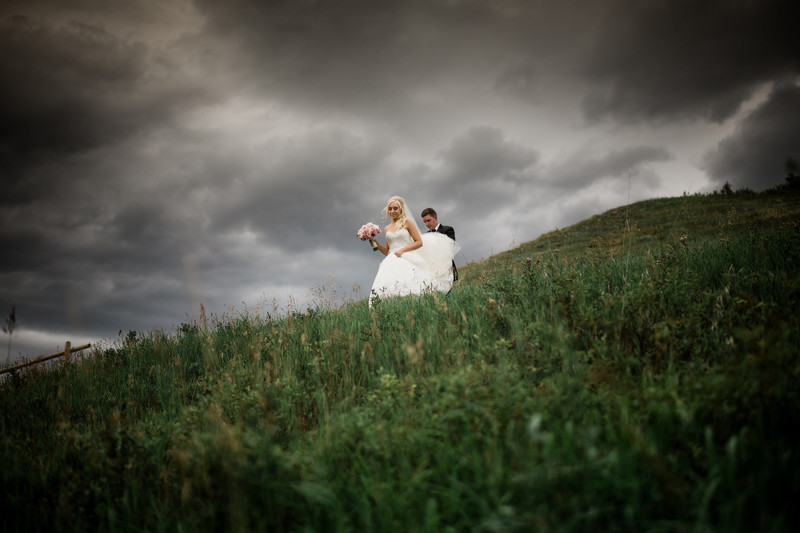 Bride + Groom Running Down A Hill With Rain Just Behind