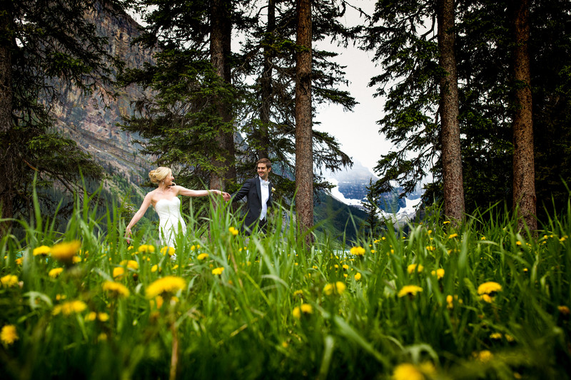 Bride + Groom Walking By Fairmont Chateau Lake Louise