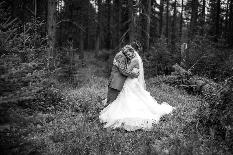Canmore Bride Being Held By Her Husband In The Rain