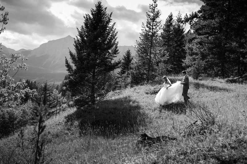 Groom Holding Bride Dress Walking Down A Hill Canmore